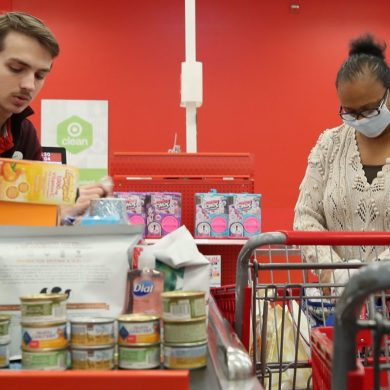 Image of a woman checking out at Target wearing a mask